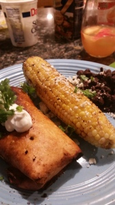 Homemade chicken chimichanga,grilled corn and black beans.